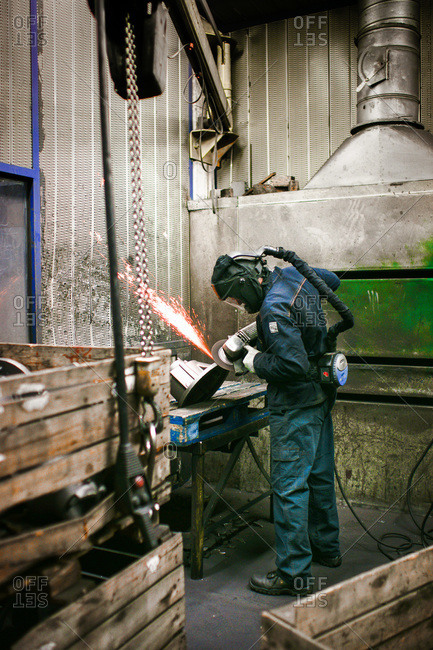 Laborer grinding a metal casting at a foundry