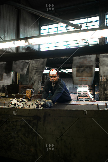 Fonderia SCM Group, Rimini, Italy - October 17, 2010: Laborer at work in a foundry