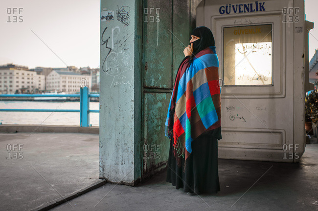 Istanbul, Turkey - January 2, 2012: Muslim woman standing next to a security booth
