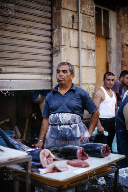 Catania, Sicily, Italy - August 6, 2011: Fishmonger smoking at a market