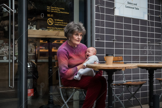 London, England - November 29, 2013: Elderly woman holding a crying baby