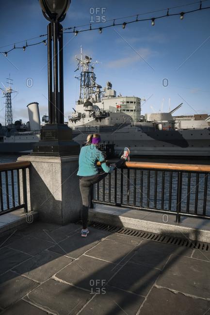 Woman stretching her legs waterside