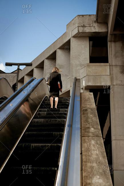 Businesswoman going up an escalator