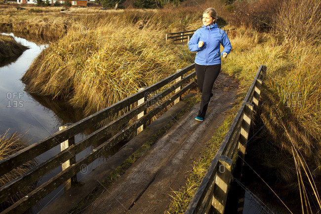 Woman jogging on wood bridge over creek