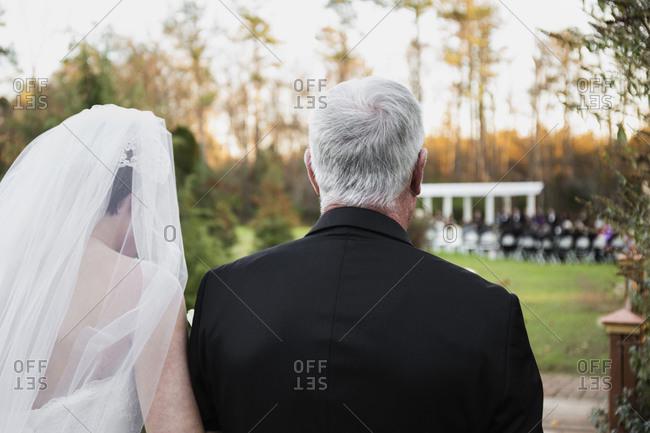 Caucasian father walking bride down aisle