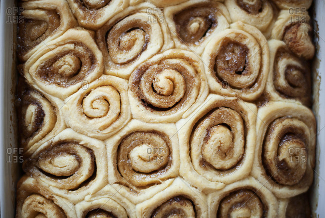 Close up of eggnog cinnamon rolls in a baking pan