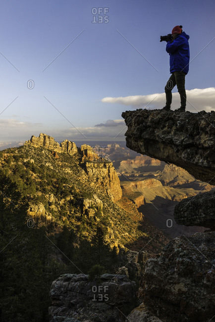 Woman taking a piture at the odge of a mountain, Grand Canyon