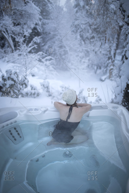A young woman with a hat looks away into the snowy forest from a hot tub.