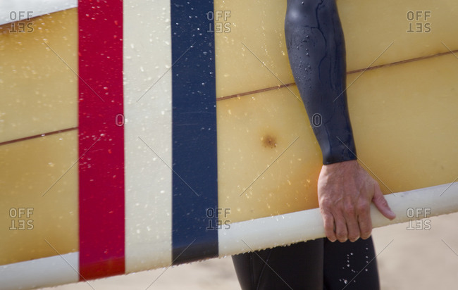 Close up of a Surfer carring colourful surf board from the beach,Cornwall,UK