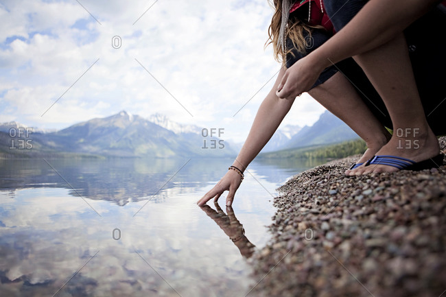 A young woman touches the pristine surface of Lake McDonald in Montana's Glacier National Park.