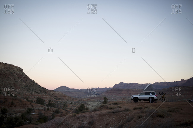An off road vehicle with a popup tent is camped overlooking the desert in southern Utah.