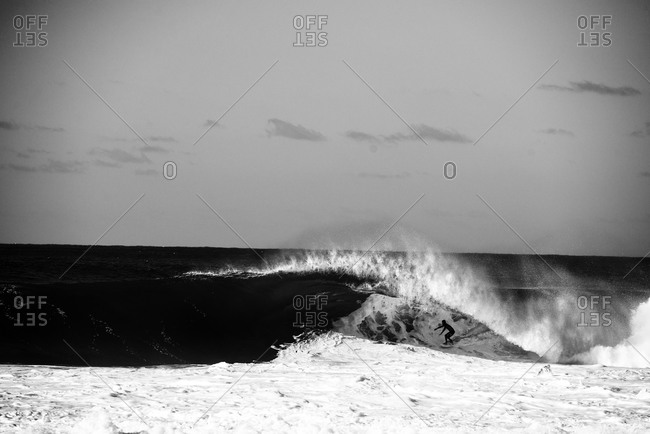 Surfer comes out of barrel at pipeline