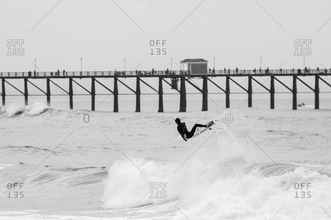Surfer boosts air in front of pier