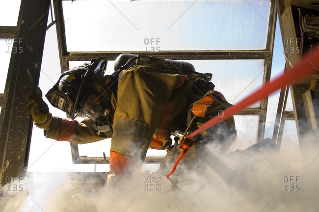 A firefighter practices fast escape drills while surrounded  by simulated explosions, smoke and fire.