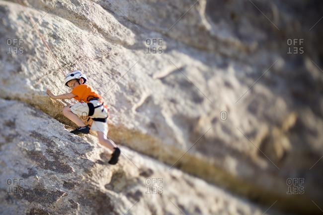 A boy climbing a rock route in Joshua Tree.