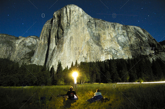 Full moonlight shines on El Capitan with climbers relaxing in the meadow below. Yosemite Valley, California.