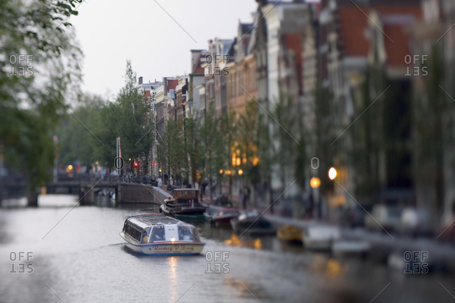 A tourist boat glides along a canal in central Amsterdam.