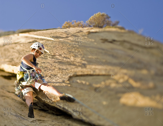 A young woman leads a climb up Cathedral Peak in the Santa Barbara Front Range. (selective focus)