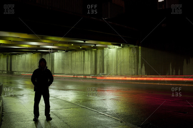 A man stands silhouetted on a sidewalk at night while blurred car lights pass in the background