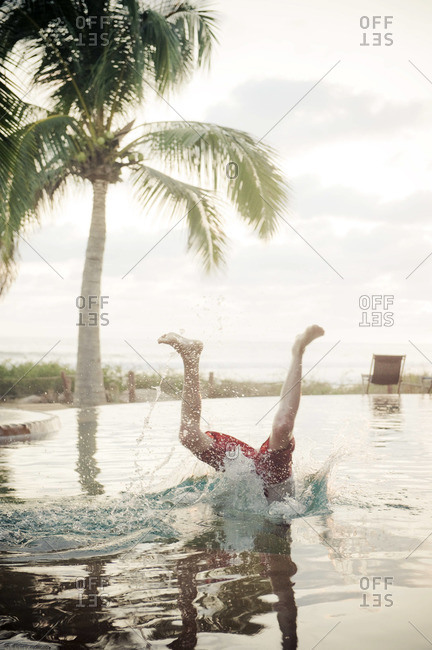 A young boy dives into  beachfront infinity pool