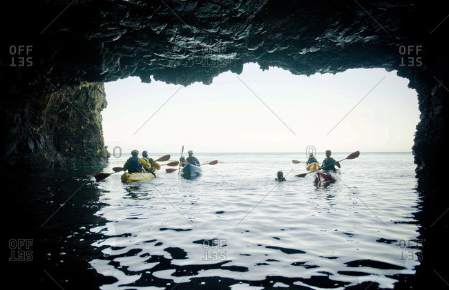 Exploring a large sea cave by kayak on Santa Cruz Island in the Channel Islands off Santa Barbara, CA.