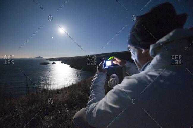 A man captures the full moon and Jupiter rising over a bay on Santa Cruz Island.