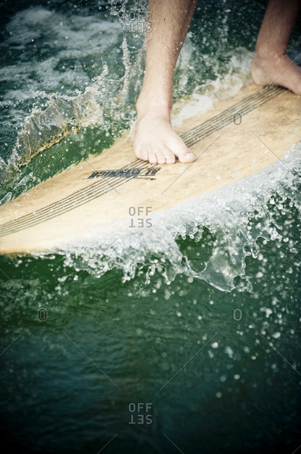 Very close shot of bare feet in action on a surfboard.