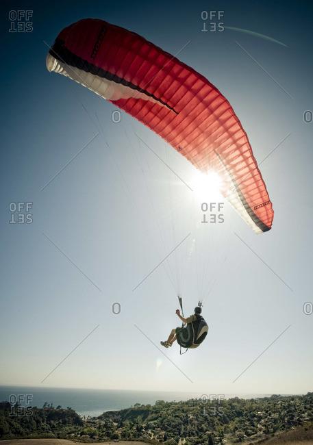 A man flying his paraglider toward the ocean in Santa Barbara, CA.