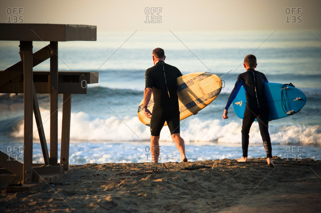 A father and son head out for a morning surf session in Newport Beach.
