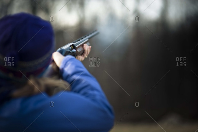 Smoke emerges from a shotgun barrel after being fired.