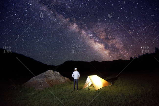 A woman, endurance athlete looks up at the Milky Way and night sky next to her tent.