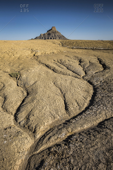A stark desert landscape with a formation in the distance.