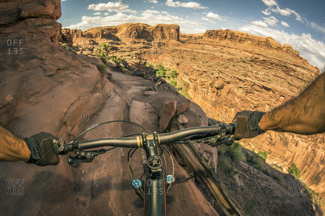 A point of view perspective of a mountain biker riding a trail in a rugged desert area.