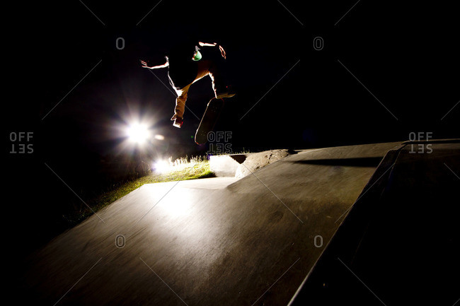 A skater flips his skateboard up a ramp under the lights at the skatepark in Whitefish, Montana.