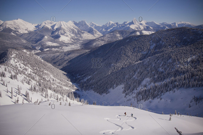 Two skiers meet at the bottom of the run on a sunny winter day.