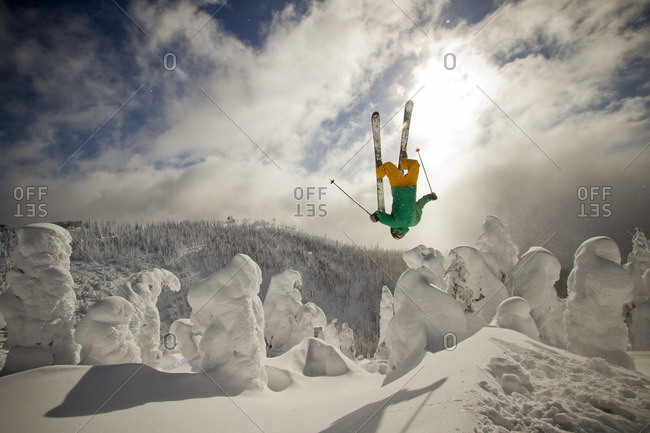 A skier throws a backflip off of a jump in the sunshine.