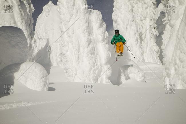 A skier bursts through snowy trees.