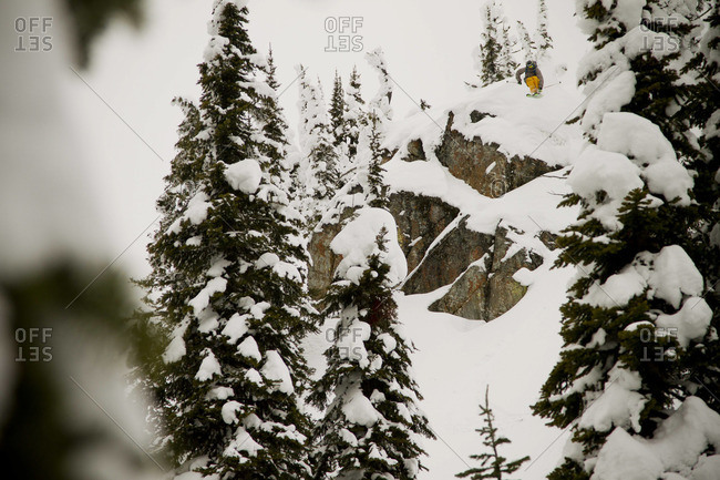 A backcountry skier drops a large cliff on a cloudy day in mid-winter.