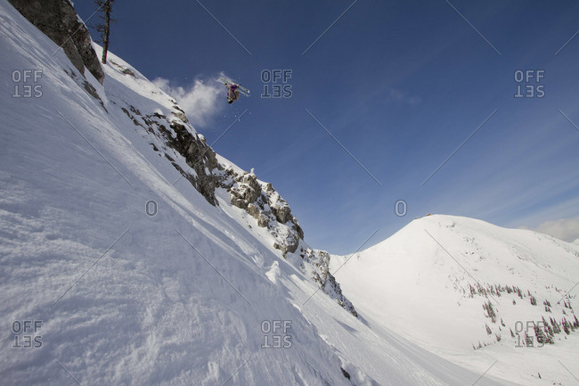 A skier hucks a backflip off of a cliff.