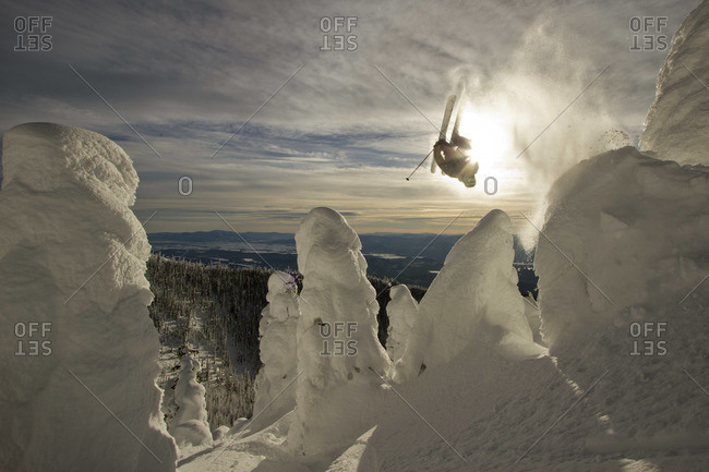 A skier throws a backflip off of a jump over snowcoated trees.