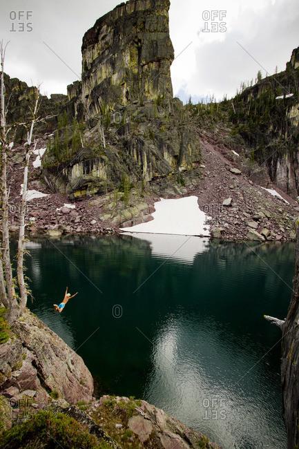 A young man jumps into a frigid alpine lake.