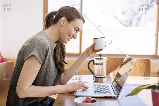 Young woman checking email at breakfast