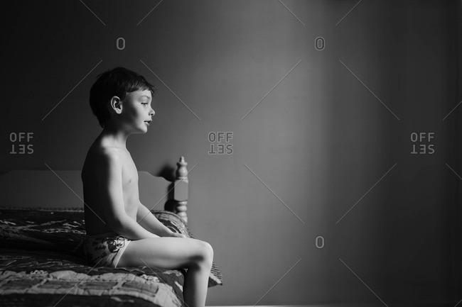Boy sitting on a bed in his underwear