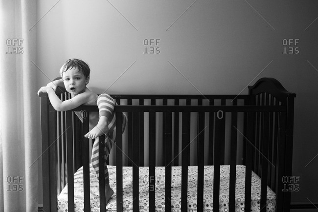 Boy climbing out of his crib