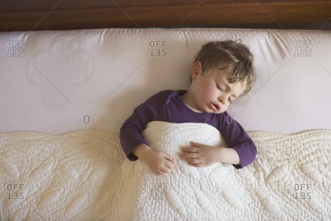 Little boy sleeping in a bed
