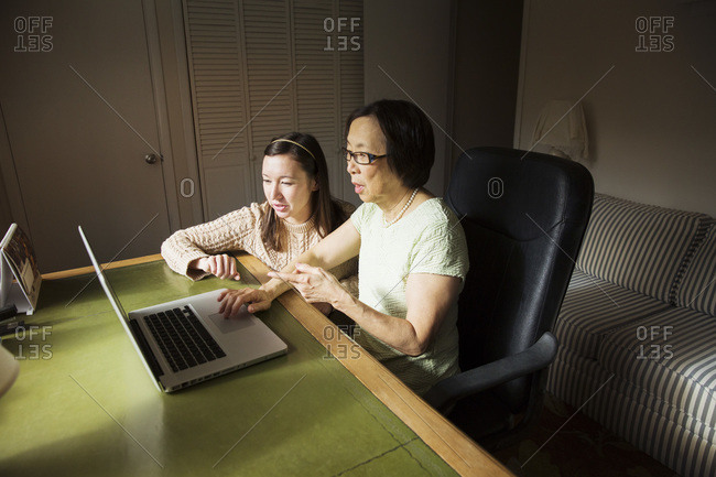 Girl helping elderly woman use the laptop
