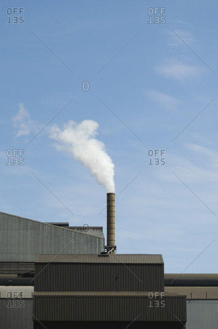 White smoke coming out of an industrial chimney