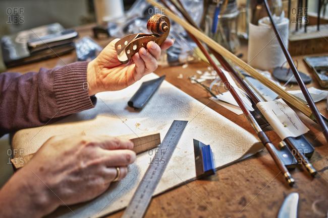 Violin maker in his workshop holding scroll, close-up