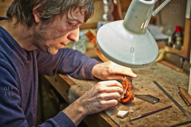 Violin maker in his workshop repairing a scroll