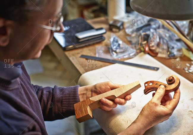 Violin maker in his workshop examining neck and scroll of an instrument